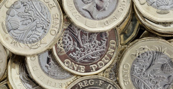 Image shows a pile of pound coins