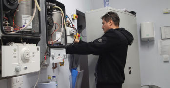 A heating engineer practicing work on a boiler