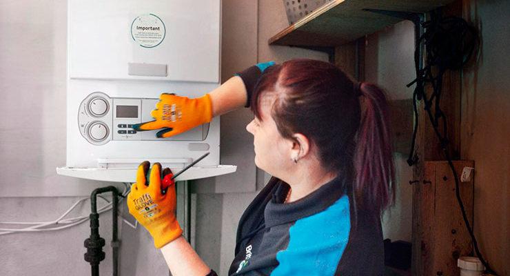 Female gas engineer working at boiler