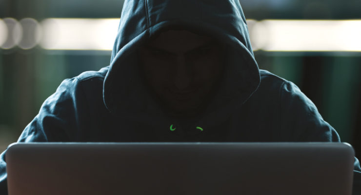 Menacing hooded figure at computer screen