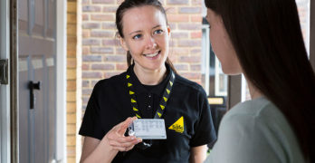 Female gas engineer showing Gas Safe ID card to customer