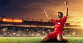 Football player celebrating on pitch wearing a Wolseley shirt